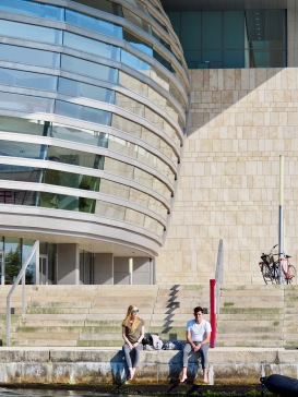 Cyclists enjoying a sunny day on the waterfront steps of the Opera building